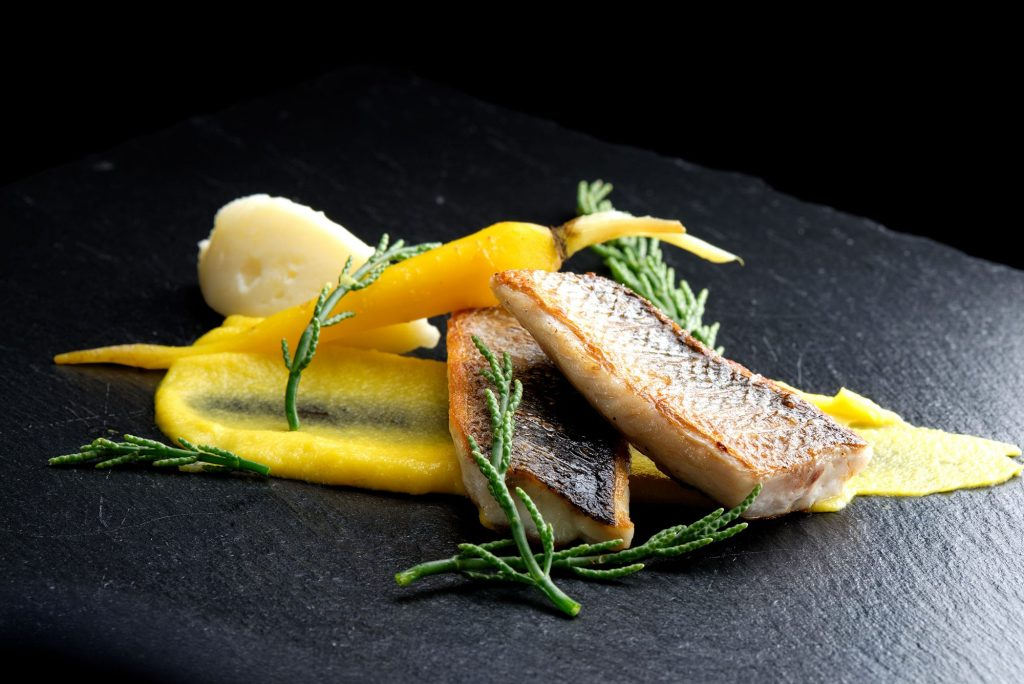 Fine dining seabass fillets on carrot potato purree and spices
